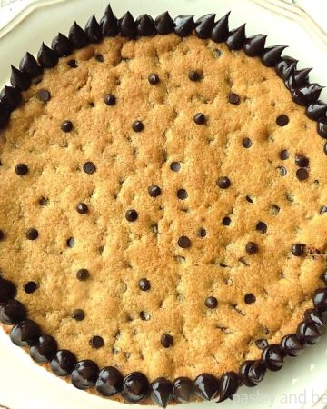 Chocolate chip cookie cake on a cake plate.
