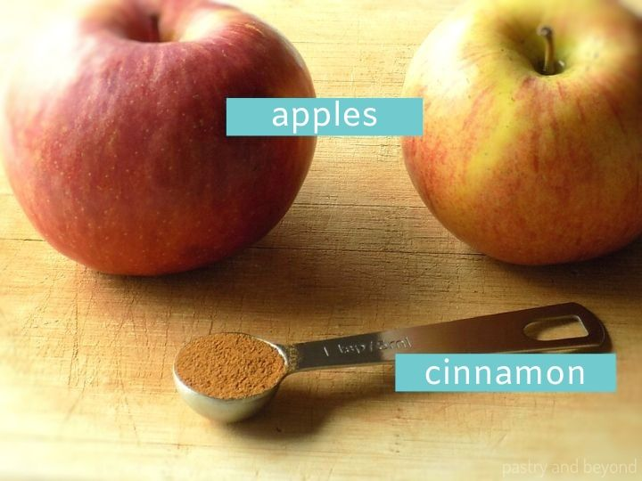 Ingredients of Dried Apples on a wooden surface; two Gala apples and 1 teaspoon of ground cinnamon