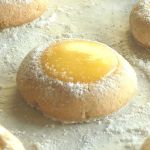 Lemon thumbprint cookies with powdered sugar on the edges.