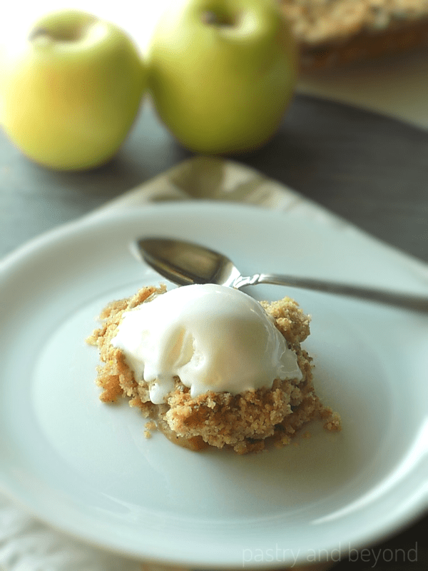 Apple Crumble topped with ice cream on a plate, golden apples are behind.