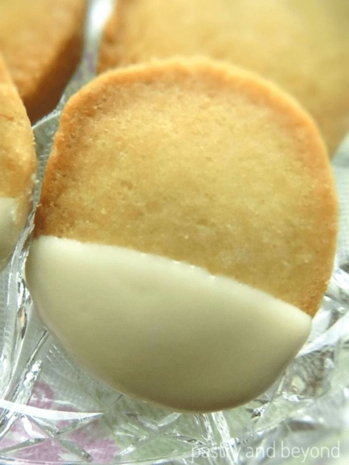 Slice-and-bake vanilla shortbread cookies dipped into melted chocolate on a glass plate.