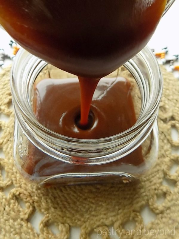 Homemade Caramel Sauce is dripping from a spoon into a jar.