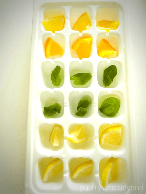 Lemon, orange and basil leaves in an ice tray.