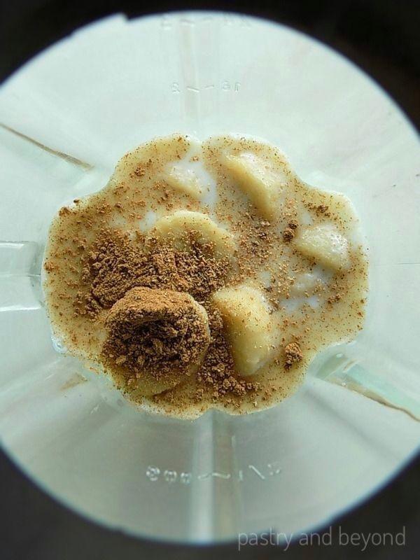 Milk, frozen bananas, cinnamon and nutmeg in a blender.