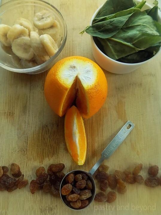 Orange, raisins, banana slices, spinach on a wooden surface.