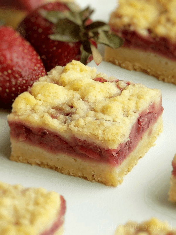 Side view of strawberry bars on a white surface.