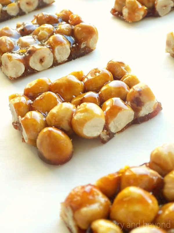 Candied Hazelnuts next to each other on a white surface.