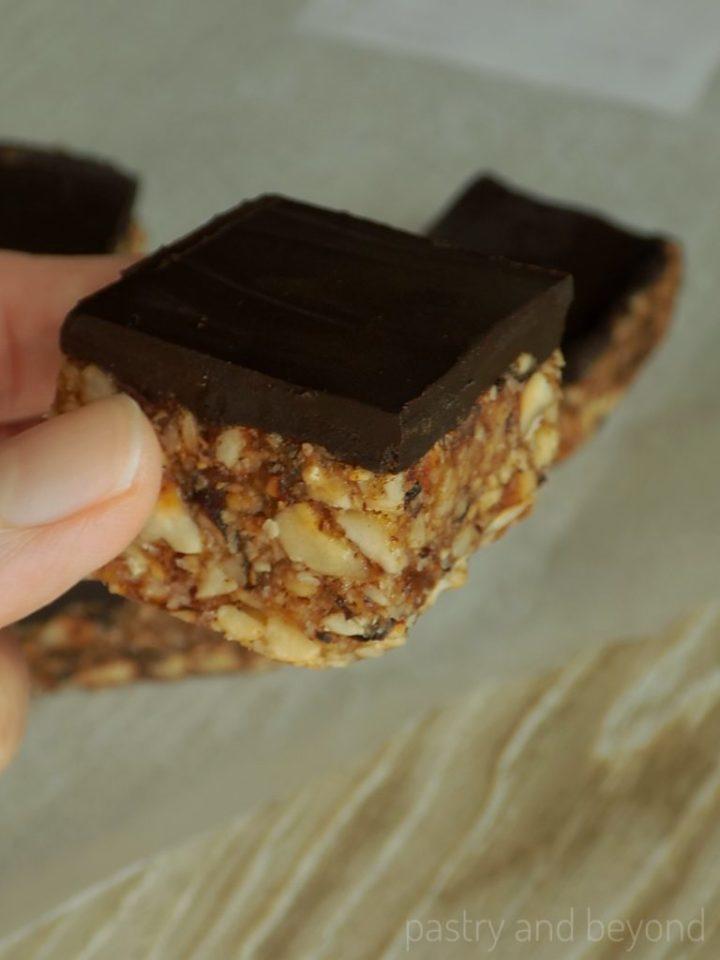 A hand holding no bake date nut bar.