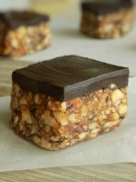 Chocolate covered date nut bars on a parchment paper that is placed on a wooden surface.