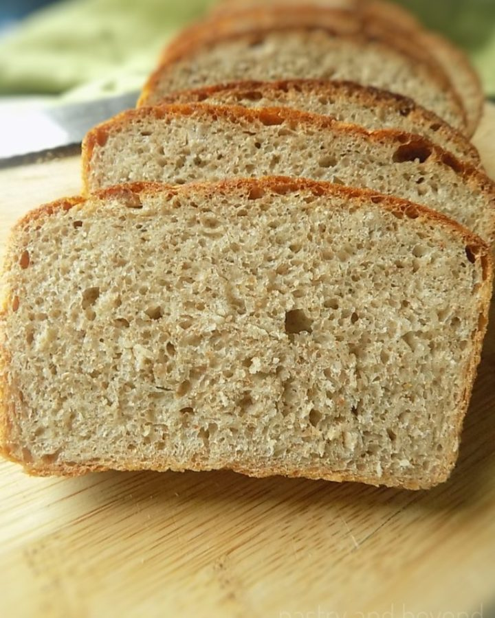 No-knead whole wheat bread slices in a row on a wooden board.