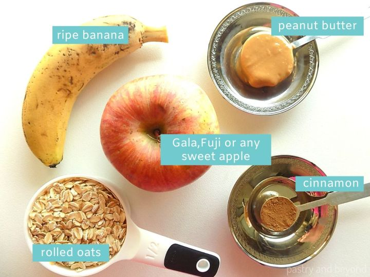 Ingredients for Healthy Apple Oatmeal Cookies on a white surface; apple, rolled oats, ripe banana, peanut butter and cinnamon
