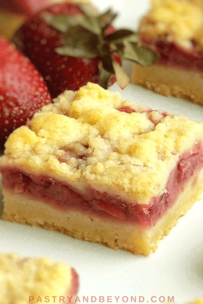 Strawberry Crumble bars on a white surface with strawberries on the background.