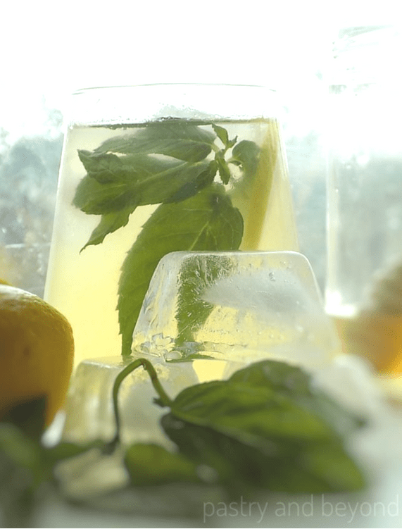 Lemonade in a glass with stacked ice cubes and mint leaves in front.