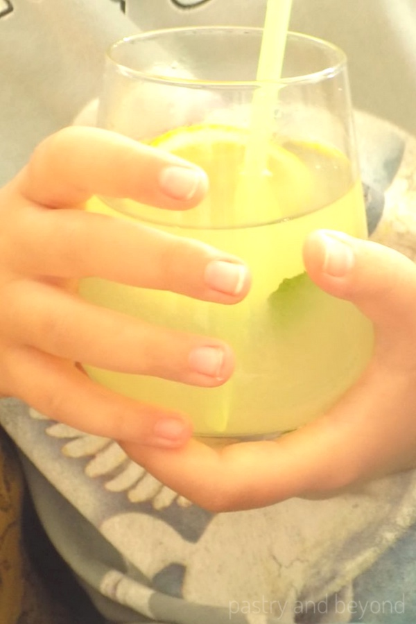 Holding a glass of lemonade with straw inside.