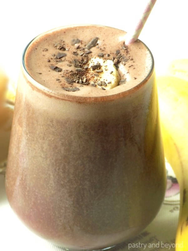 Chocolate peanut butter banana smoothie in a large glass with a straw.