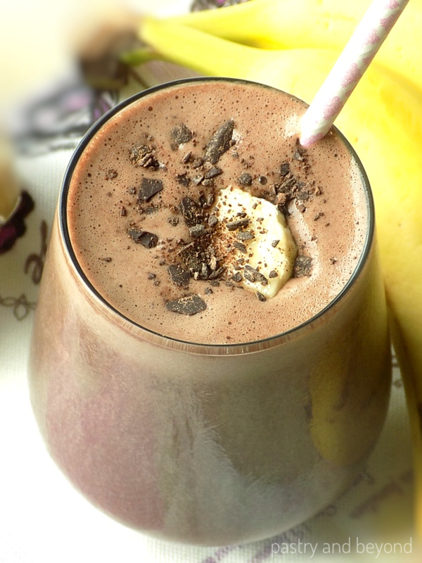 Chocolate Peanut Butter Banana Smoothie with shredded chocolate and banana slice inside.