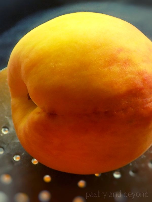 Peach on a slotted spoon.