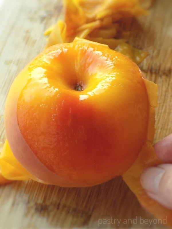 How to Peel Peaches step by step: Peeling a peach with fingers after blanching peaches.