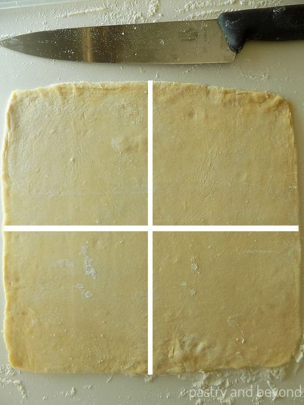 Example of how to make 4 squares from a rolled out square dough by cutting diagonally and vertically with white lines.
