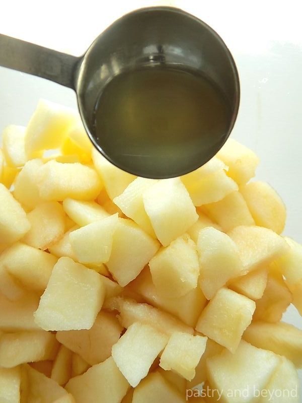 Adding lemon juice into the chopped apples for apple turnover filling