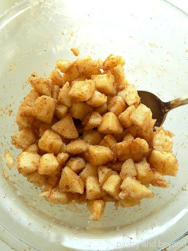 Cubed apples in a bowl mixed with sugar, cinnamon, nutmeg and cornstarch with a spoon.