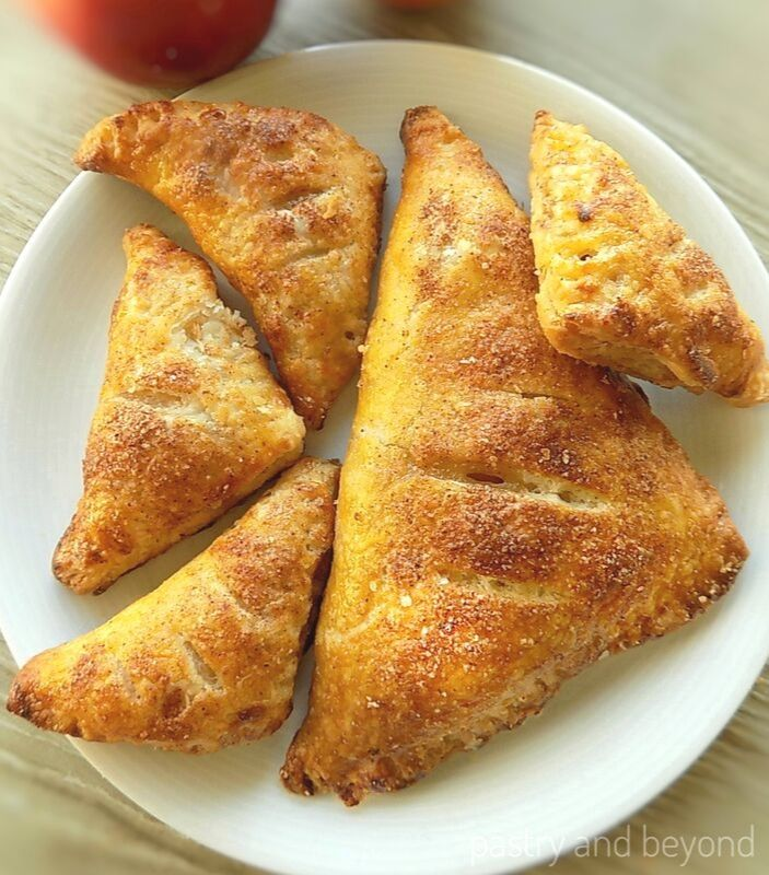 1 Large 4 small puff pastry apple turnovers on a plate.