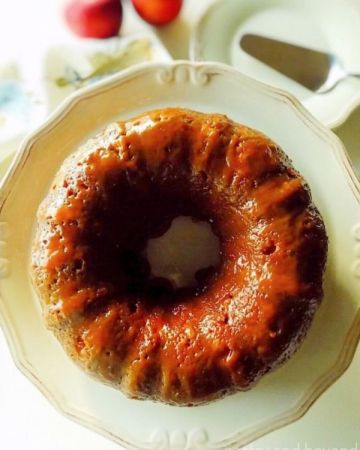 Caramel Apple Bundt Cake on a cake serving plate, small cake plate and apples on the background.