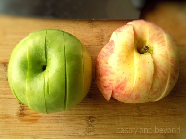 Sliced green and red apple on a chopping board.