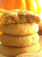 Stacked pumpkin spice cookies, the one on top is in half and pumpkin in the background.