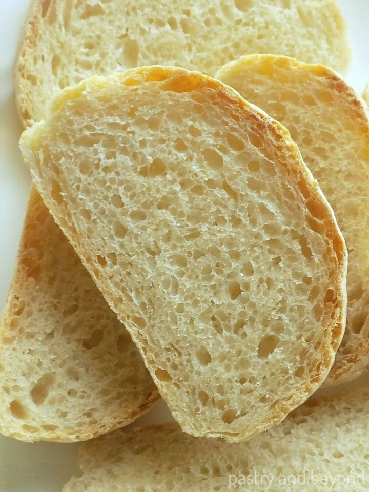 Homemade No Knead Bread slices on a white surface.