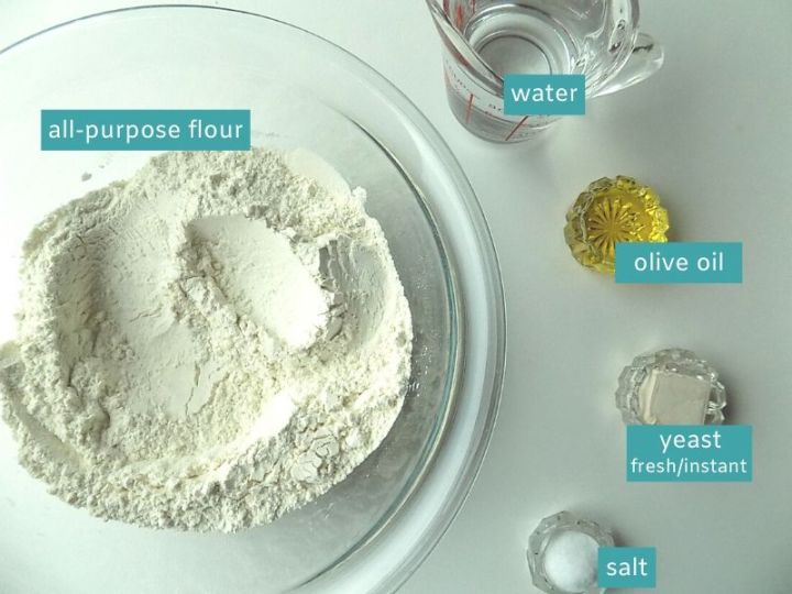 Ingredients for pizza dough on a white surface; flour, water, olive oil, fresh yeast and salt.