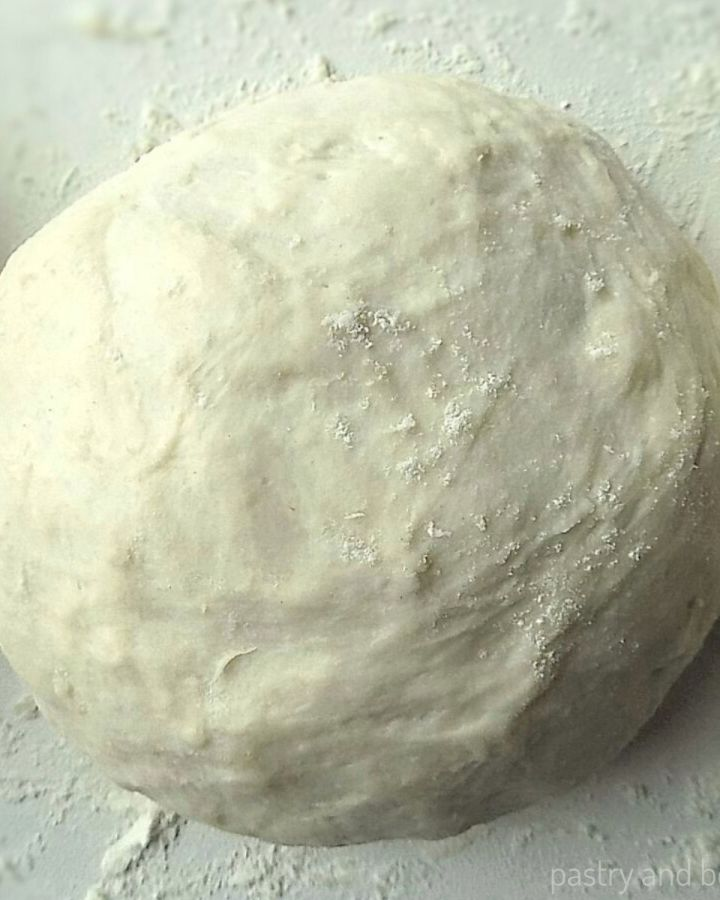 Pizza dough that is made by hand and rolled into a ball on a floured surface.