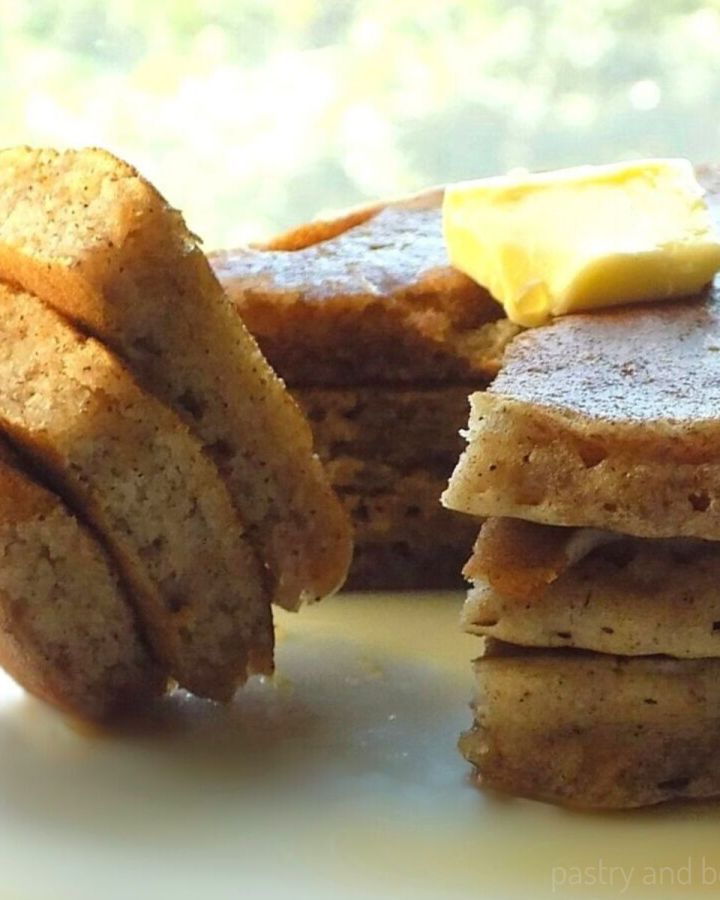 Side view of stacked cinnamon sugar pancakes and slice of stacked pancakes on a fork.