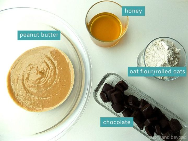 Ingredients for chocolate peanut butter no bake bars on a white surface in glass dishes; peanut butter, honey, oat flour and chocolate.
