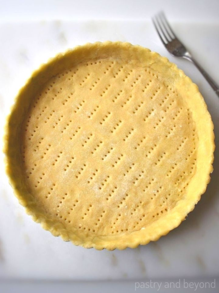 Unbaked pricked tart dough on a marble surface with a fork.