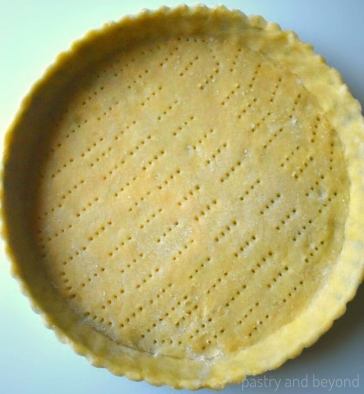 Tart dough that is pricked with a fork in a tart pan.