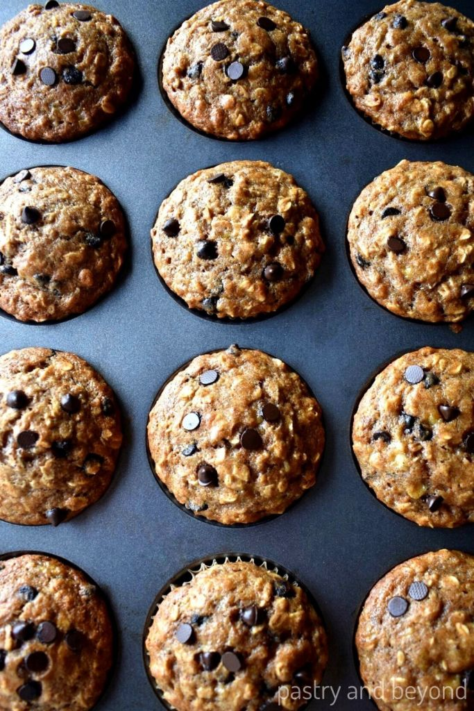 Baked banana and oatmeal muffins with chocolate chips in a muffin tin.
