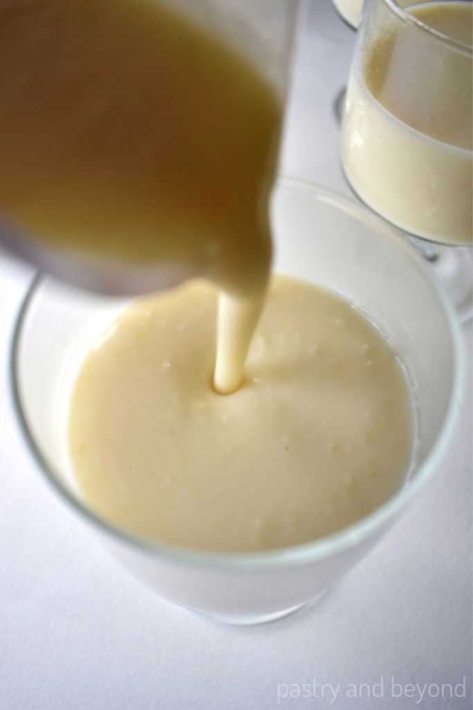 Pouring almond pudding from a jug into a serving glass.