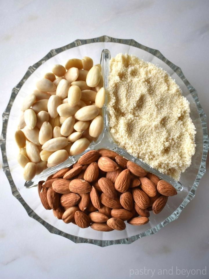 Blanched almonds, almond flour and raw almonds in a glass plate with three segments.
