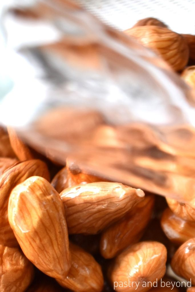 Pouring water over almonds to let them cool.