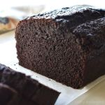 Chocolate loaf cake on a parchment paper with slices.