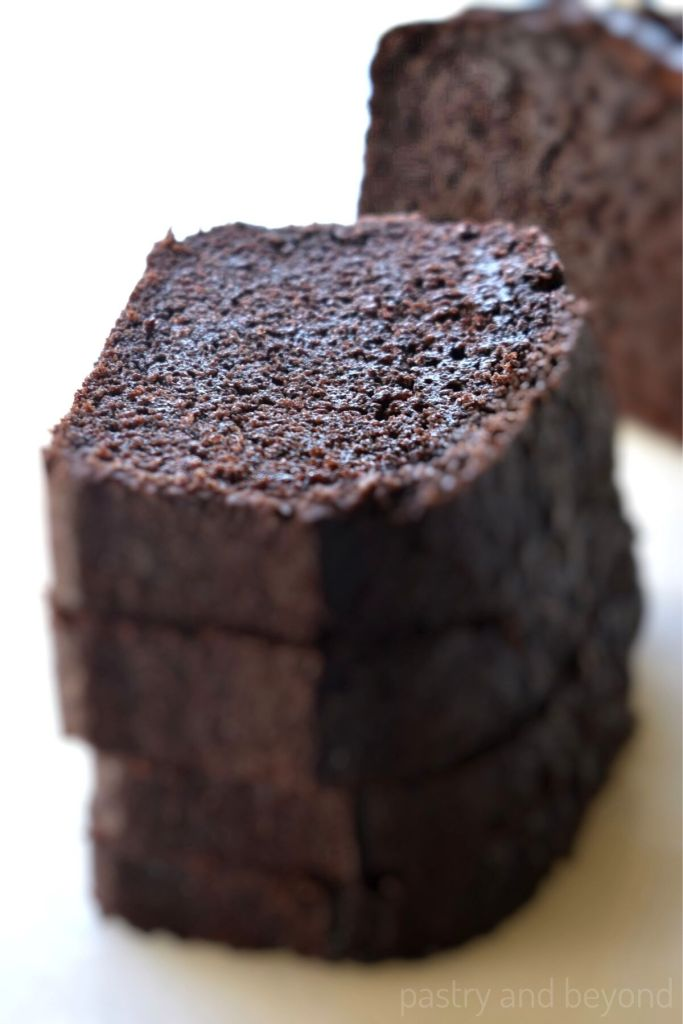 Stacked chocolate cake loaf slices on a white surface.