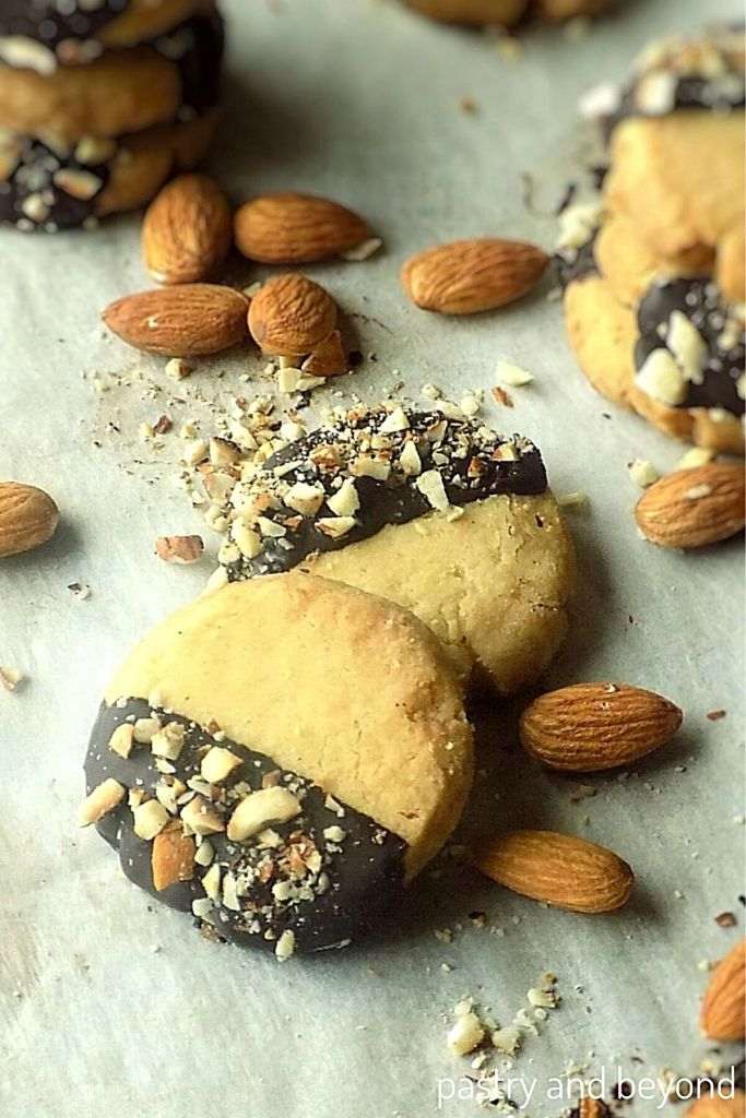 Almond extract cookies on a white surface with whole almonds.