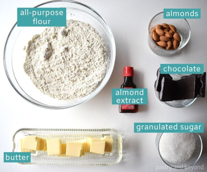 Ingredients of almond extract cookies on a white surface.