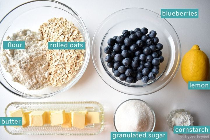 Ingredients of blueberry oatmeal bars on a white surface.
