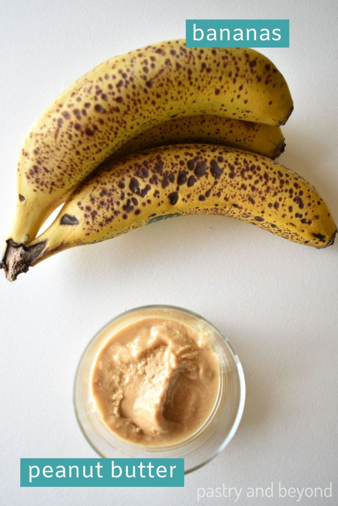 Bananas and peanut butter on a white surface.