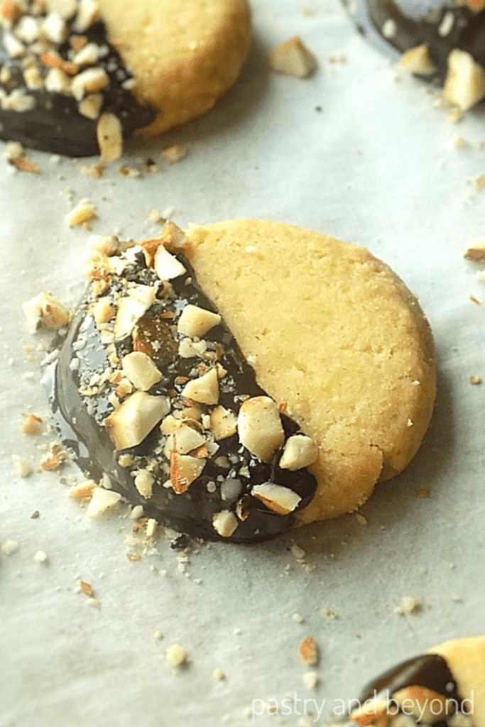 Almond shortbread cookies next to each other on a parchment paper.