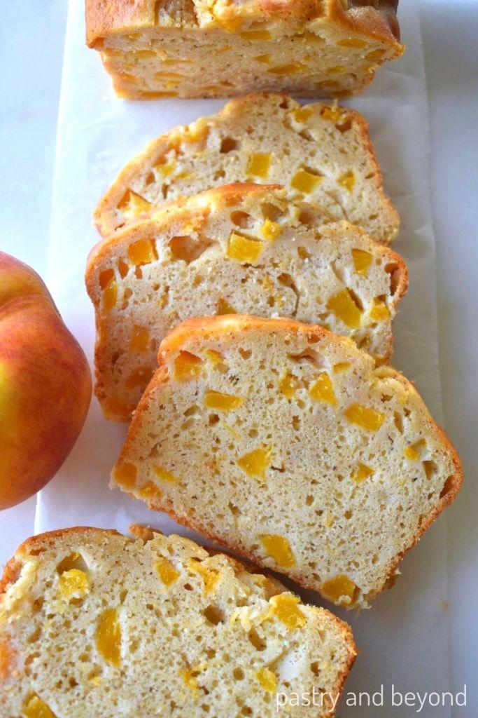Sliced peach bread on a white surface.