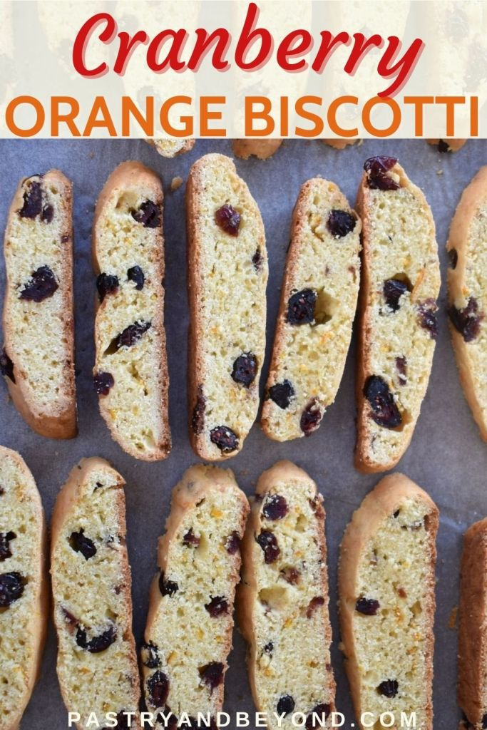 Cranberry orange biscotti cookies on a parchment paper with text overlay.