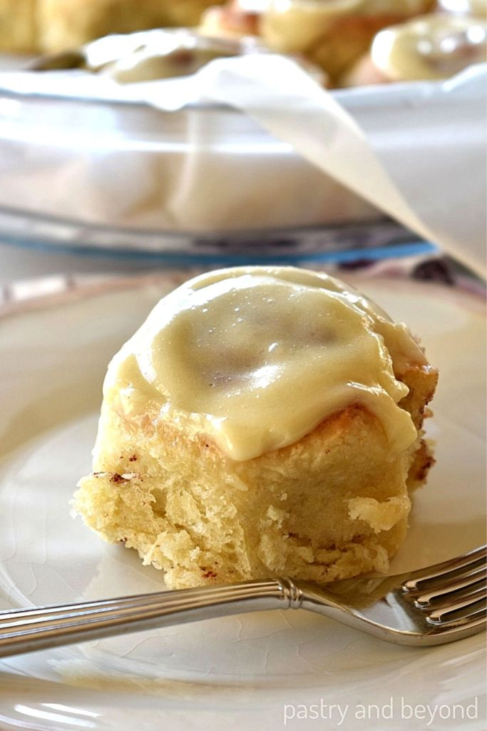 Cinnamon roll in a plate with a fork.